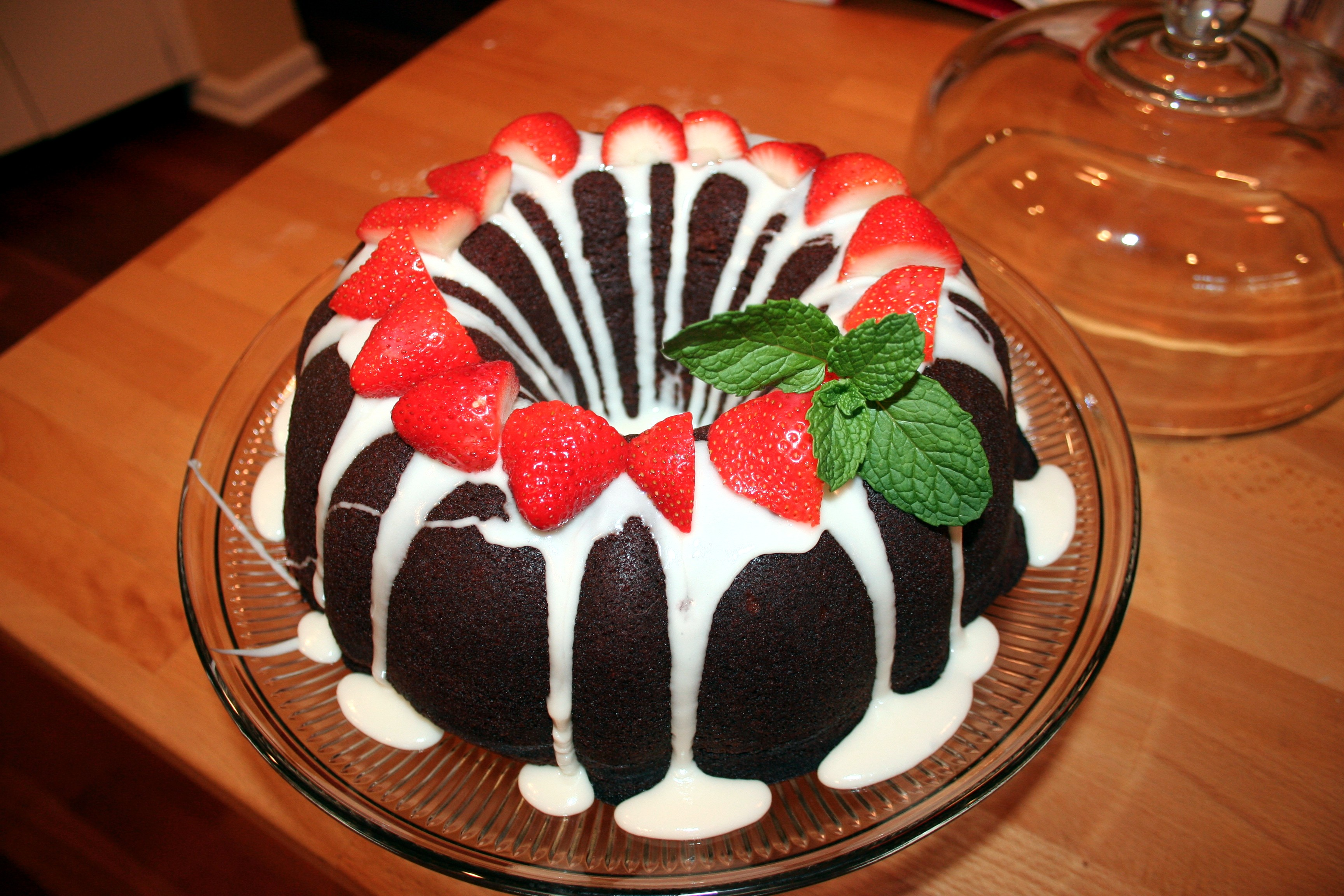 Dark Chocolate Bundt Cake With White Icing And Strawberries